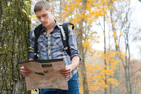 20 years old: Young man looking at map