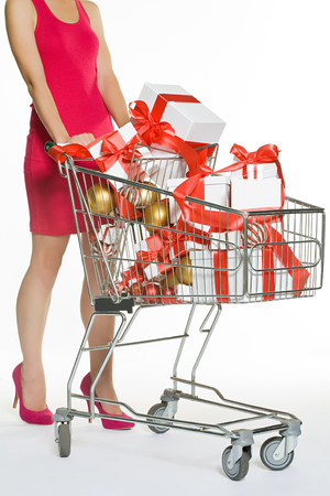 Woman with shopping trolley full of christmas gifts