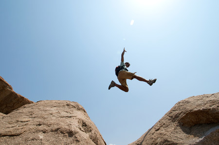 trouble free: Man leaping between large boulders