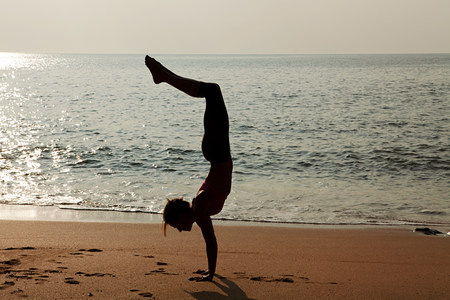 seaboard: Woman practicing yoga on a beach at sunset