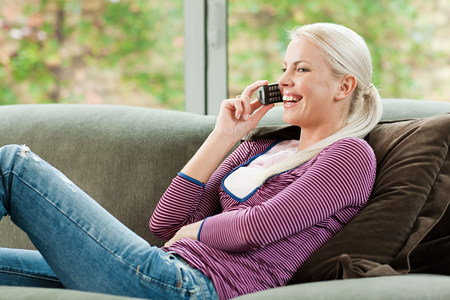 Young woman on cell phone at home LANG_EVOIMAGES