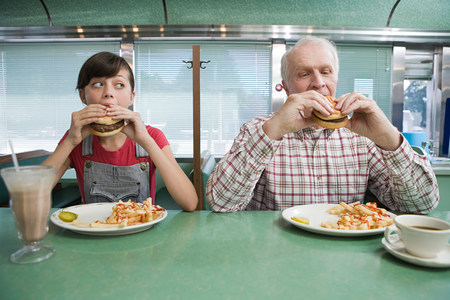 age 10 12 years: Girl and old man eating burgers in a diner
