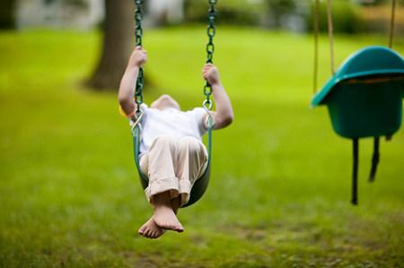 playground rides: Child on swing