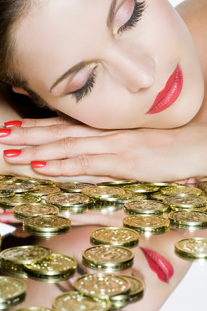 coins shot in golden color: Coins and woman woman with eyes closed LANG_EVOIMAGES