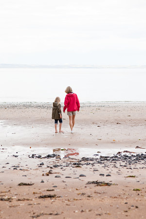 Mother and daughter walking towards the sea