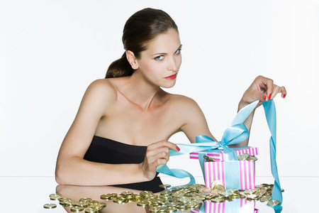 looking at viewer: Young woman and gift box of coins