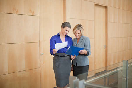two persons only: Businesswomen looking at paperwork