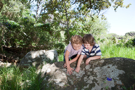 play the old park: Two boys leaning on rock