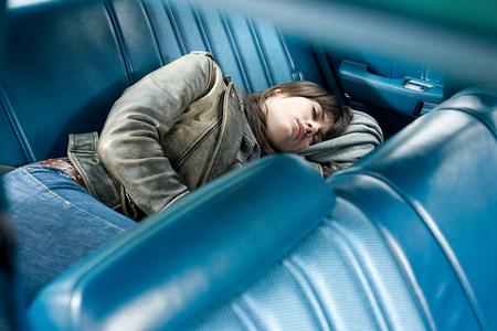Young woman asleep in car