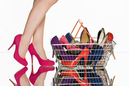 indecisive: Legs of woman and shopping basket full of shoes