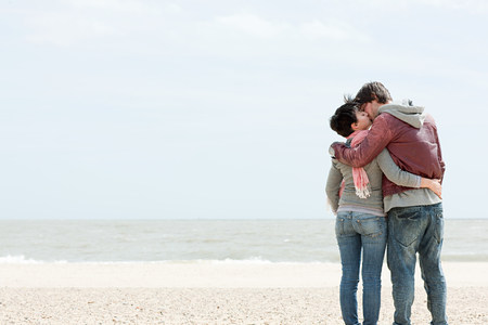 travel features: Young couple kissing by the sea