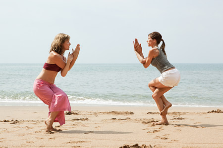 Two women practicing yoga on a beach