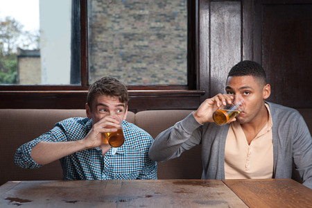 20 25 years old: Young men drinking beer in bar