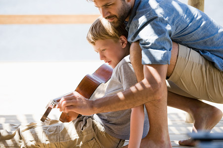 30 years old man: Father and son playing guitar