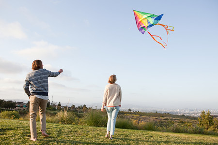 woman hanging toy: Young couple flying a kite