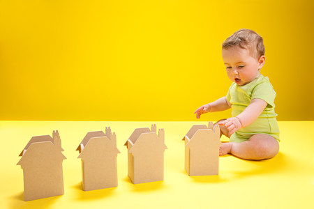 futures: Baby boy playing with cardboard houses