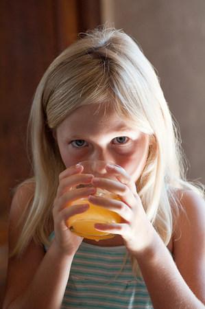 Chica con vaso de jugo de naranja