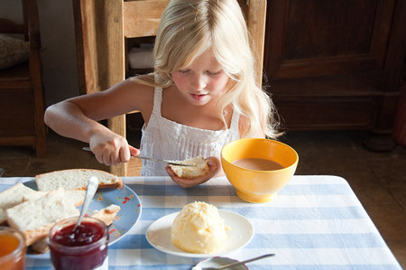 Girls spreading butter on bread