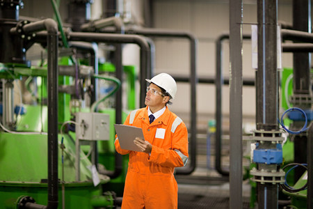 30 years old man: Engineer inspecting machinery in factory LANG_EVOIMAGES