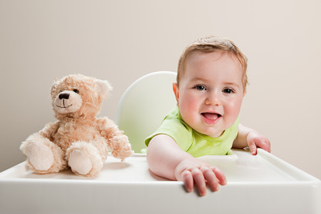 6 year old: Baby boy sitting in highchair with teddy bear