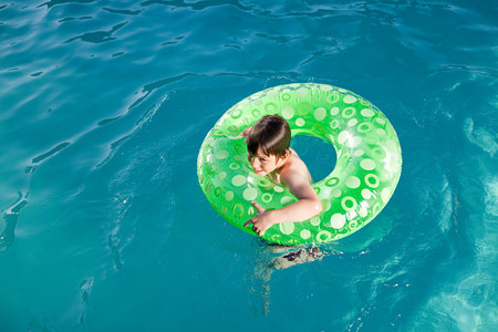 Boy in inflatable ring in outdoor swimming pool