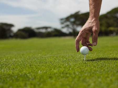 off course: Man playing golf, picking up ball LANG_EVOIMAGES