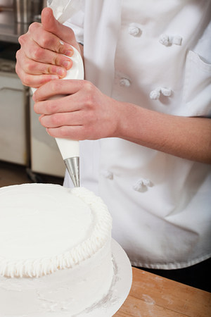 Female chef icing a cake