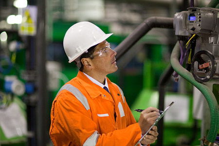 Engineer inspecting machinery in factory LANG_EVOIMAGES