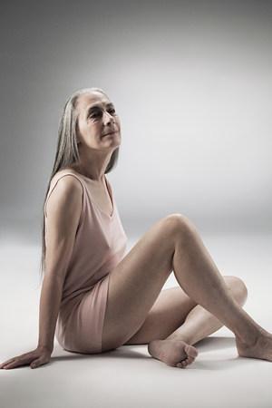 Senior mujer sentada en el suelo