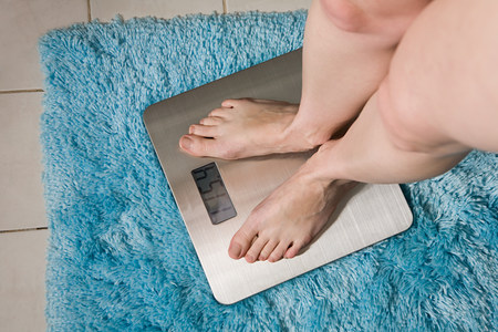 above 18: Young woman weighing herself on bathroom scales LANG_EVOIMAGES