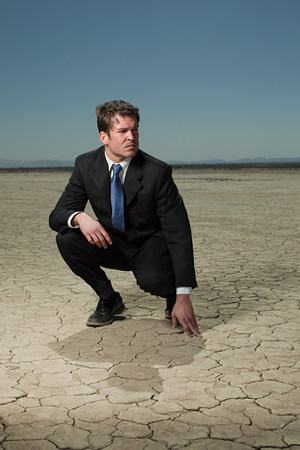 a mirage: Businessman crouching in desert landscape