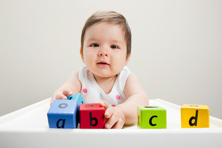 6 year old: Baby boy sitting in highchair with wooden alphabet blocks