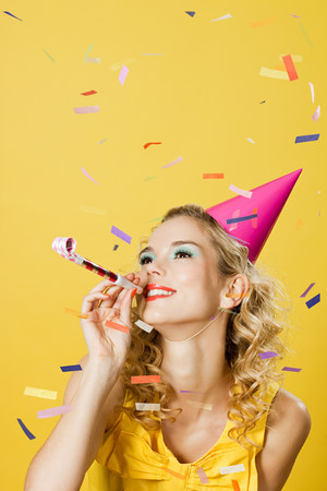 Young woman wearing party hat with party blower and confetti