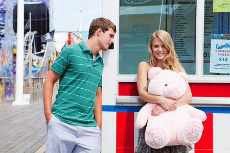 Teenage couple at pier with teddy bear