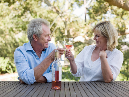 60 64 years: Couple toasting with wine outdoors
