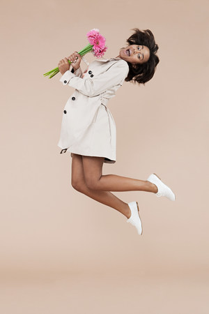 Young woman holding flowers and jumping