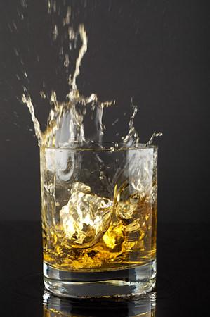 Ice cube splashing in tumbler of whiskey