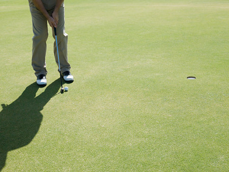 cropped out: Man playing golf, on putting green LANG_EVOIMAGES