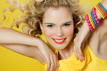 bowing head: Young blonde woman against yellow background LANG_EVOIMAGES