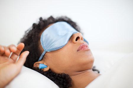 Mujer durmiendo en máscara de ojo y tapones para los oídos LANG_EVOIMAGES