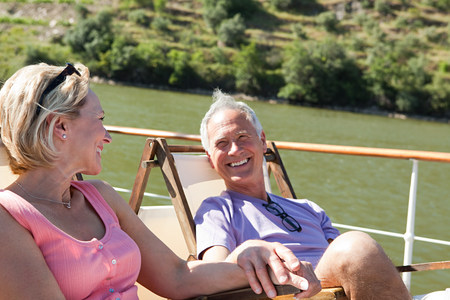 Senior couple sitting on deckchairs on a boat LANG_EVOIMAGES
