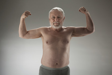 front facing: Senior man flexing muscles