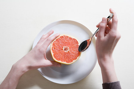 furniture part: Young woman eating grapefruit