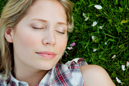 Young woman lying on grass with eyes closed