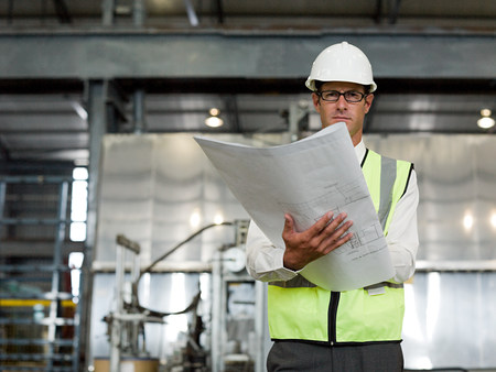 Mature man with blueprint in factory
