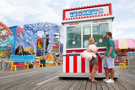 woman hanging toy: Teenage couple at fun fair ticket booth