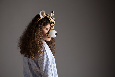 Young girl wearing tiger mask