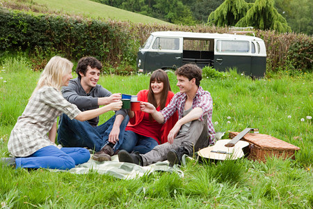 20 years old: Friends toasting with mugs outdoors