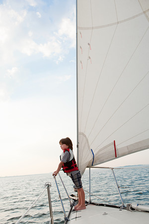 new age: Young boy on board yacht, looking at view LANG_EVOIMAGES
