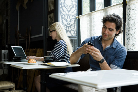telecommuter: Man with cellphone and woman with laptop in cafe LANG_EVOIMAGES